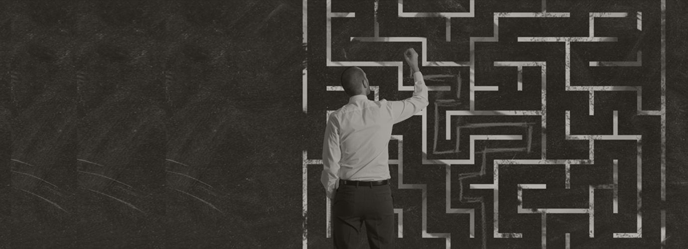 A man trying to figure out solution to maze puzzle on a wall with a piece of chalk